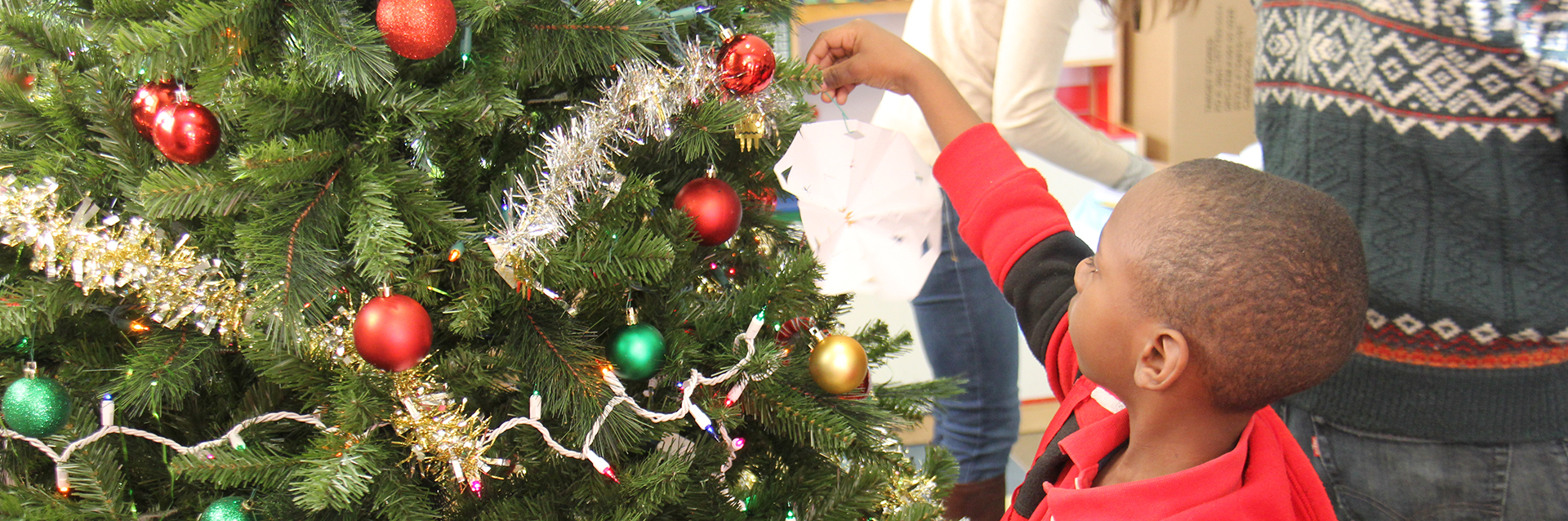 A child living in SOME's affordable housing decorates a Christmas tree
